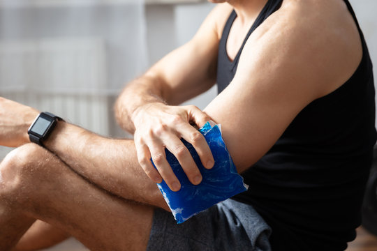 Man Applying Ice Bag On Elbow