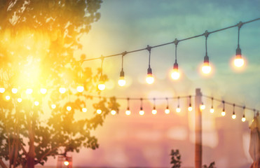 blurred bokeh light on sunset with yellow string lights decor in beach restaurant Fototapete