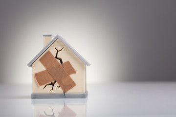 House Model With Crossed Band Aid