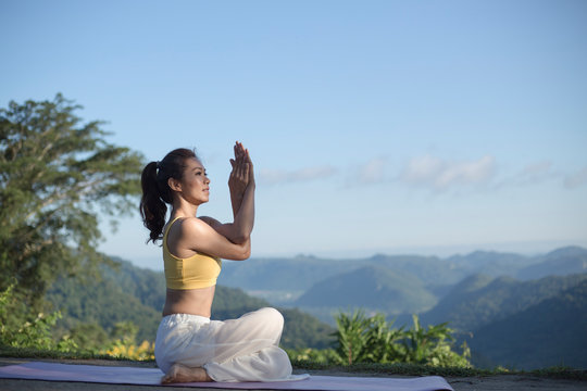 Side view of women practicing yoga. sitting in eagle pose. Anusara Yoga. .beautiful landscape on morning with mist on mountain peaks on natural view, .concept for exercising, health care