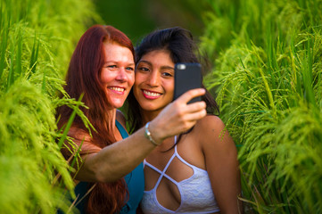 beautiful tourist women taking girlfriends selfie together with mobile phone in rice field nature landscape smiling enjoying holidays in diversity ethnicity love