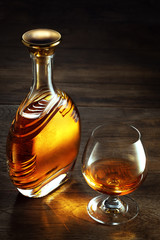 view of glass of  whiskey and a bottle aside on color wooden  background.
