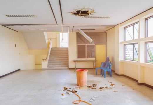 water leak drop interior office building in red bucket from gypsum ceiling and flow on terrazzo floor