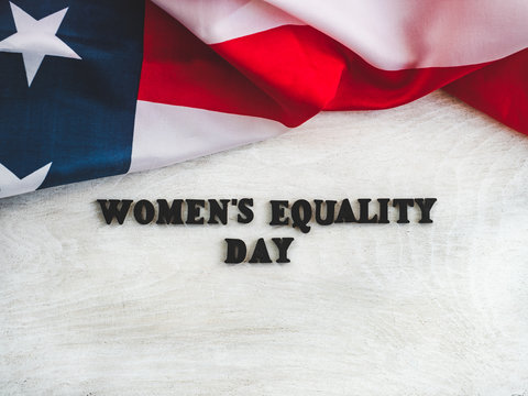 Beautiful card for Women's Equality Day. Wooden letters with a congratulatory inscription on a white background. Close-up, top view. Congratulations for loved ones, relatives, friends and colleagues