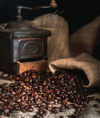 coffee beans and vintage coffee grinder. Roasted coffee beans in a vintage setting. Dark still life - Image.