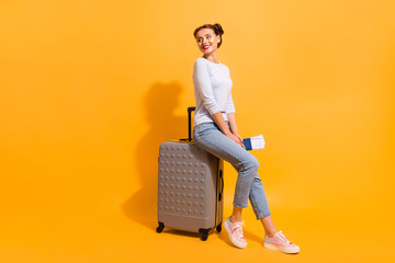 Profile side full length body size photo of cute charming youngster in light denim clothes standing in queue for her jet sitting on trolley bag holding documents on vivid background