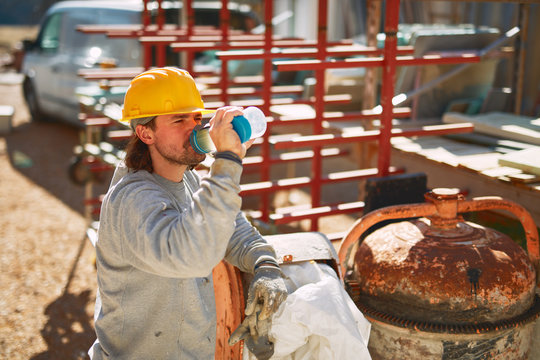 Construction worker on a heavy site doing hard work and drinking water.