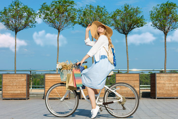 Smiling woman is cycling around city on  white bicycle. Girl in blue dress is going shopping with colorful packages on handlebars of bike. Female retro bicycle with basket with bouquet of flowers.