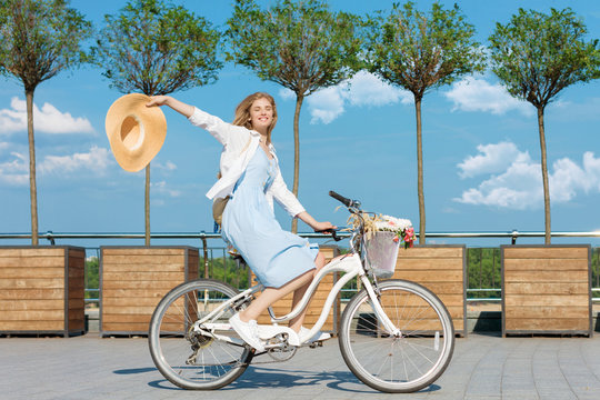Happy smiling woman girl dressed stylish retro pin up cloth dress riding white bicycle with basket of flowers. Warm summer spring autumn day. Green trip healthy concept. Trees, blue sky white clouds.
