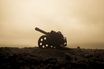 Battle scene. Silhouette of old field gun standing at field ready to fire. With colorful dark foggy background. Selective focus Wall mural