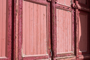 Red old street door with peeled paint in daylight The door is an old wooden red color with peeling paint is illuminated by the bright summer sun