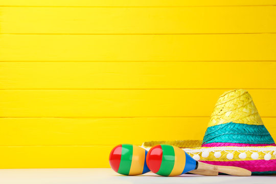 Mexican hat and maracas on yellow background