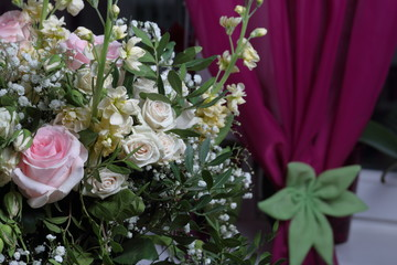 A large bouquet of different flowers. Several types of roses and other plants to decorate the bouquet.