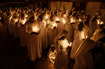 Christian faithful of the Legio Maria African Mission church hold candles as they attend the Easter vigil mass in their church in Fort Jesus area of Nairobi