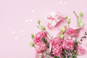 Gift box and beautiful flowers on pastel pink table top view. Greeting card for Mother day. Flat lay.