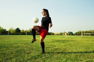 Female soccer player hitting a ball