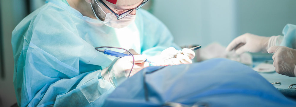 Young male plastic surgeon operates in the operating room of a medical center.