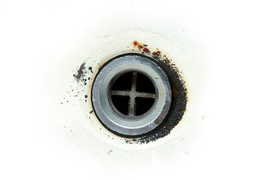Closeup of a rust  drain in a sink isolated on a white background