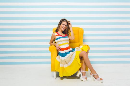 Expressing brightful positive emotions of joyful fashionable young woman in colorful dress having fun in yellow chair on striped blue white background. Summer time, joy, smiling, happiness