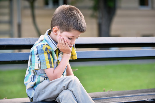 sad child boy sitting on a bench