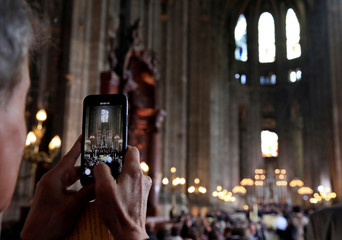 A man takes a photo before Easter Sunday Mass at Saint-Eustache, days after a massive fire devastated large parts of the structure of the gothic Notre-Dame Cathedral, in Paris