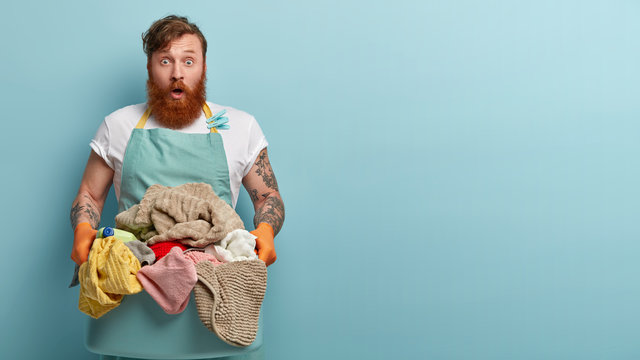 Stupefied foxy housekeeper keeps jaw dropped, holds basin with dirty laundry, has cleaning detergent, wears casual domestic clothes, isolated over blue background with free space aside for text