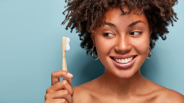 Teeth care and oral hygiene concept. Positive young Afro American woman with curly haircut, holds wooden toothbrush, cleans teeth, has dark skin, being in high spirit. Healthcare and dentistry