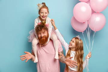 Two funny naughty sisters play together, tickle each other being cared by dad. Cute little girl holds bunch of air balloons. Happy family of father and two daughters prepare for holiday, pose indoor