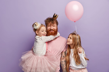 Small girl hugs red haired dad who smiles happily, glad to have two daughters, dressed in festive...