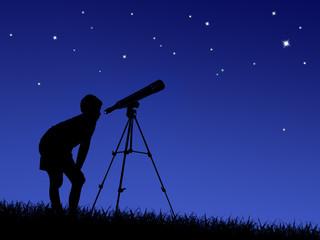 boy looks at the stars through a telescope