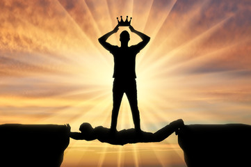 Selfish man puts a crown on his head, he stands on a man in the form of a bridge over a precipice