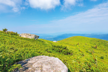 mountain landscape on summer morning. meadows on the hills decorated with big white sharp rocks. beautiful green and blue nature scenery on a sunny day. explore back-country
