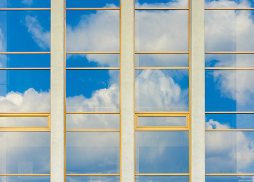beautiful urban architecture background. window reflection of a clouds on a blue sky