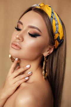 sensual girl with dark hair and evening makeup, with silk headband