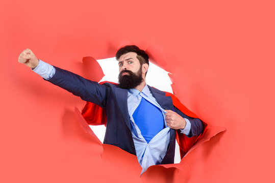 Through paper. Business growth. Businessman. Bearded man looking through paper. Super businessmen in red cape showing blue shirt. Superhero. Superman Cape. Hero. Symbol S. Super power.