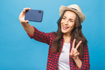 Charming young woman in white hat travel and take selfie on front camera smartphone showing v-sign isolated on blue pink background.