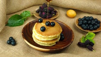 Fototapete - Pour fresh honey on a pile of pancake with blueberry in wooden bowl and tropical fruit on sackcloth