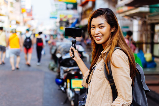 Young Asian female tourist woman holding a gimbal with smartphone and recording videos for blog. Travel blogger and vlogger concept