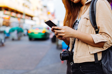 Young Asian female tourist woman using a mobile phone in Bangkok, Thailand. Calling a cab or finding information during traveling concept Fototapete