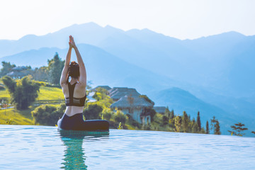 Fototapeta Beautiful Asian woman practice yoga Lotus pose on the pool above the Mountain peak in the morning in front of beautiful nature views in SAPA vietnam,Feel so comfortable and relax with yoga in holiday