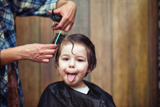 A little boy is trimmed in the hairdresser's