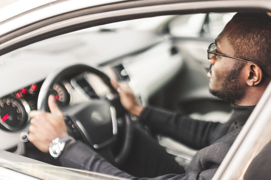 A young businessman in a suit sits at the wheel of a expensive car.