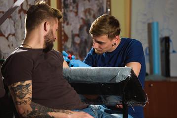 Tattooist makes a tattoo.