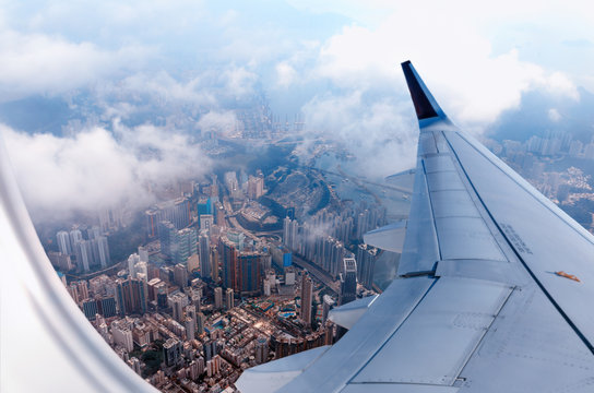 Plane to Hong Kong. Airplane window view at the skyscrapers. Overhead city view. Cityscape aerial. Concept of travel and air transportation..