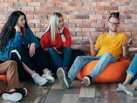 Modern work culture. Group of millennials relaxing on bean bags. Communication and discussion. Business team diversity.