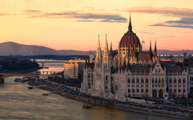 Cityscape of Budapest with bright parliament illuminated by last sunshine before sundown and Danube river with bridge. Pink and purple colors of sky reflecting in water during sunset.