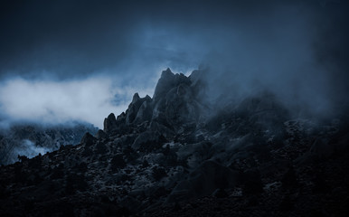 Rocky mountain peaks surrounded by misty fog in the Sierra Nevada mountains near North Lake in Eastern California. The ominous foggy weather creats an emotional feel to the mist filled rugged scene Wall mural