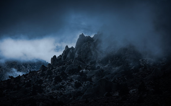 Rocky mountain peaks surrounded by misty fog in the Sierra Nevada mountains near North Lake in Eastern California. The ominous foggy weather creats an emotional feel to the mist filled rugged scene