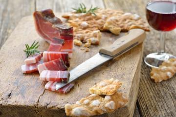 Südtiroler Jause: Deftiger Speck mit knusprigem Schüttelbrot, dazu regionaler Rotwein – Typical South Tyrolean snack with country bacon and local crunchy flat bread, served with local red wine