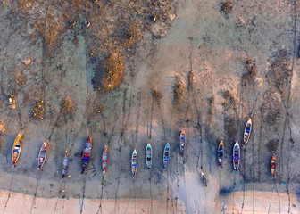 Aerial view of ocean shore and fishing boats at low tide